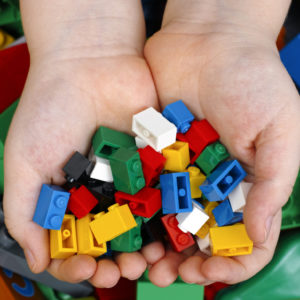 Tambov, Russian Federation - February 20, 2015 Lego Bricks in child's hands with Lego Duplo blocks and toys background. Studio shot.